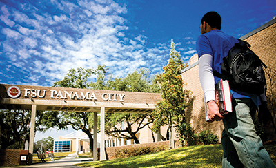 a student wearing a blue shirt walks onto FSU Panama City's campus on a sunny day